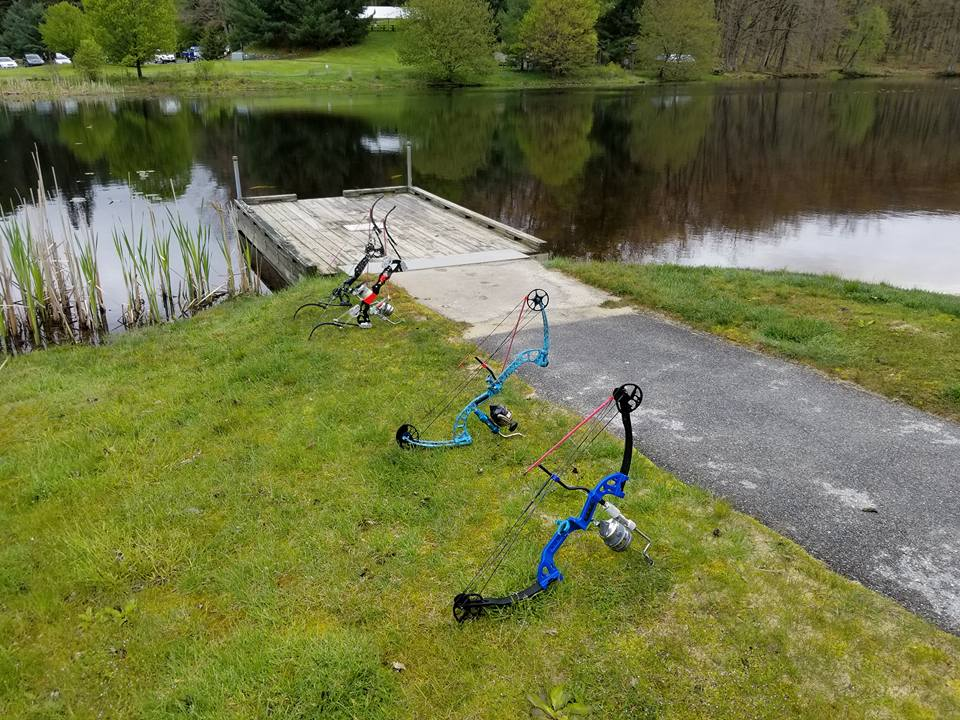 four fishing bows laid out on a grassy bank