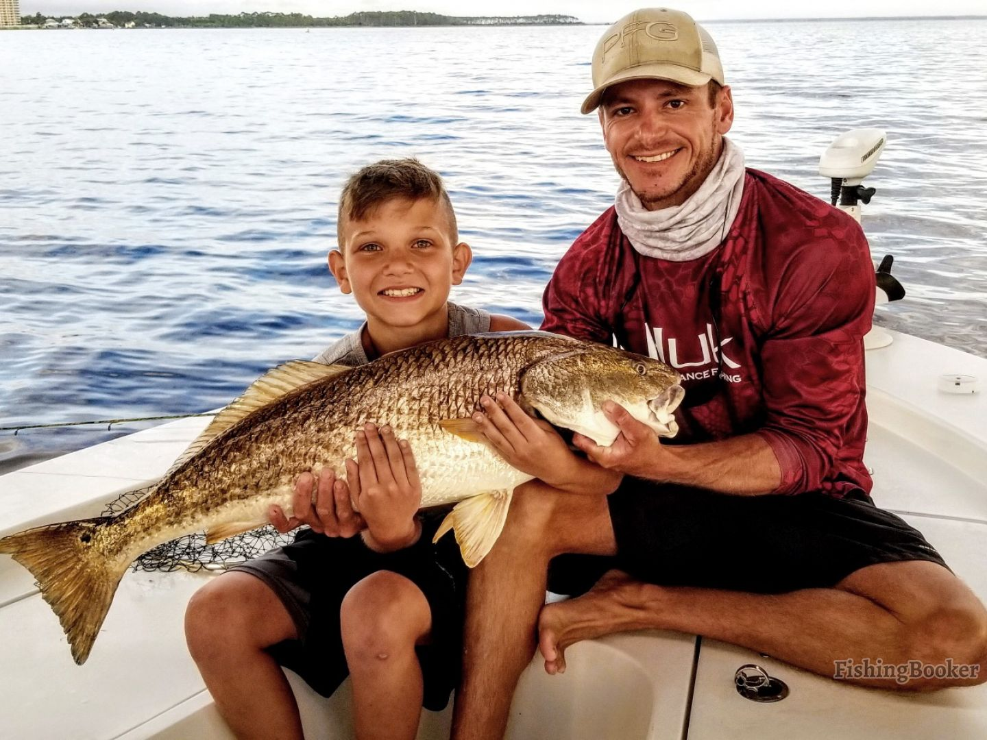 A fishing charter captain is helping a young boy angler hold a Redfish