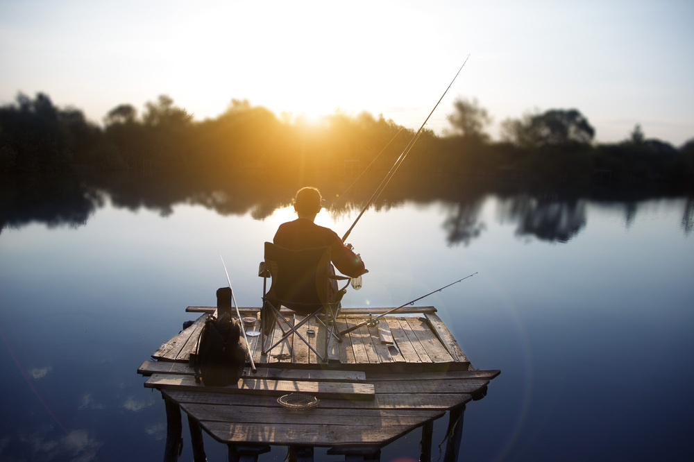 an angler fishing from a small wooden platform at dawn