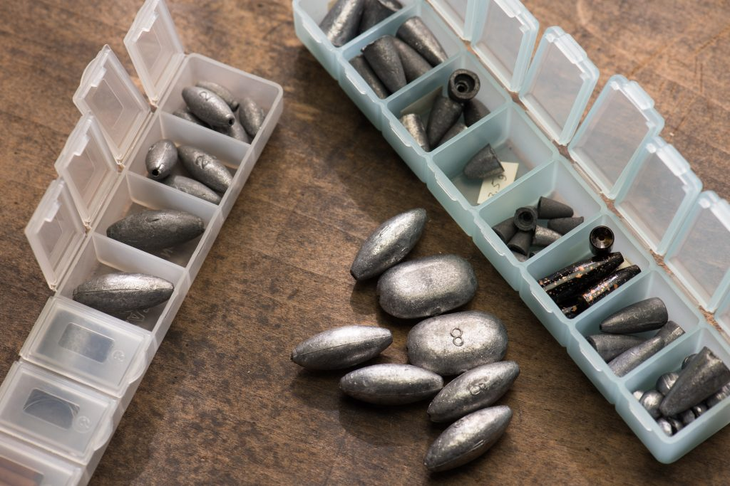 two boxes of fishing sinkers on a table