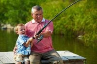 A grandfather teaching his grandson how to fish on a river bank.