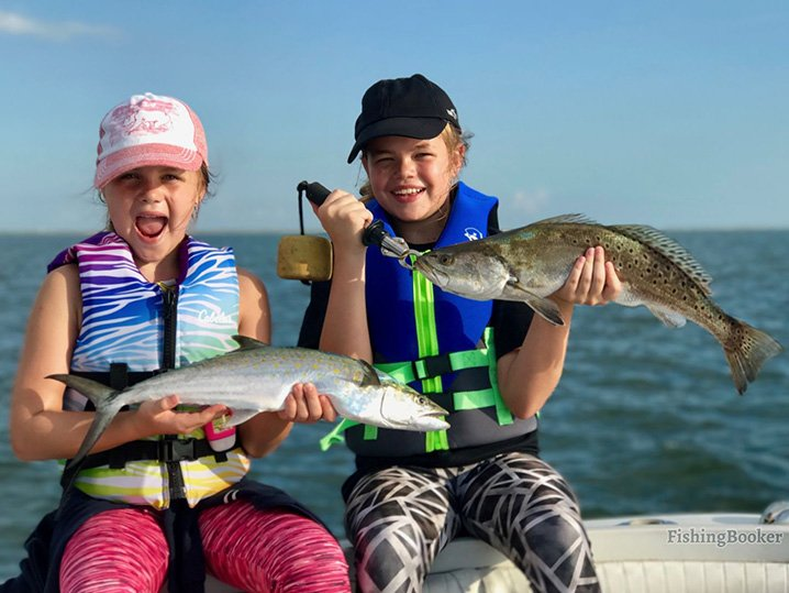Two young smiling girls holding speckled Trout and Redfish which they caught during their family fishing trip in Galveston.
