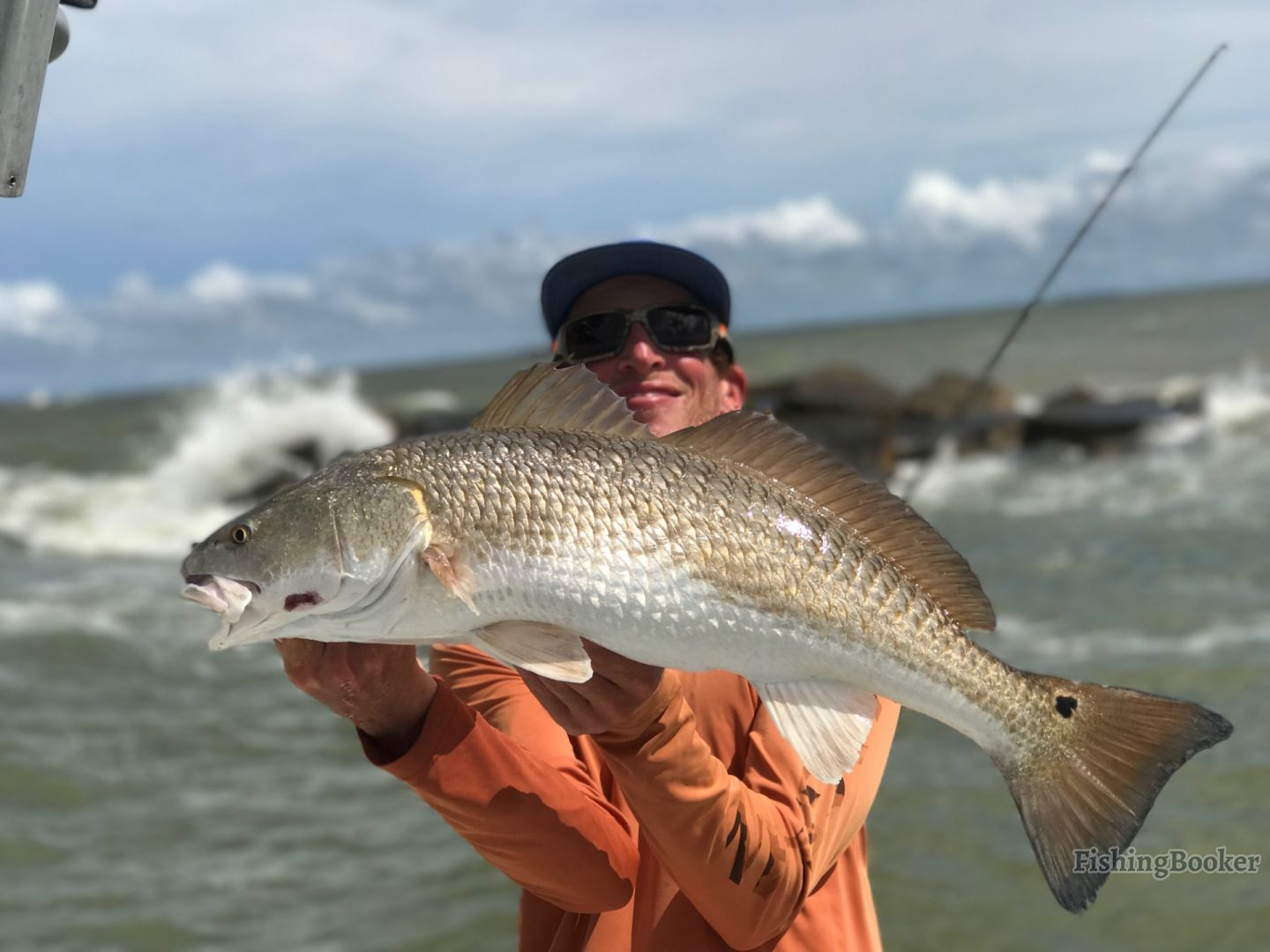 Lady angler holding a big Redfish she caught in Galveston.