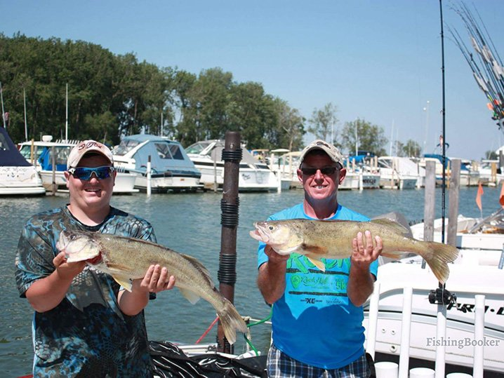 Two anglers holding Walleyes they caught on their fishing charter on Lake Erie.