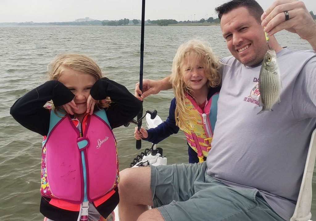 Two kids making funny faces and their father holding a small fish on a boat