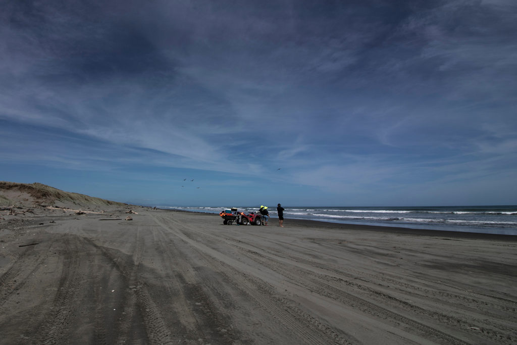 A pair of kontiki anglers with quad bikes on a beach in New Zealand