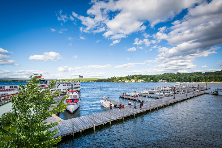 Pier on the Lake Winnipesaukee, and fishing boats around it, with trees in the background