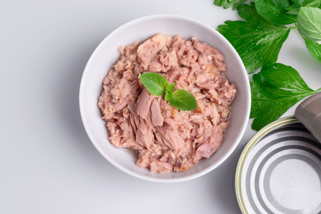 Tinned tuna in a bowl, with a tin and herbs next to it