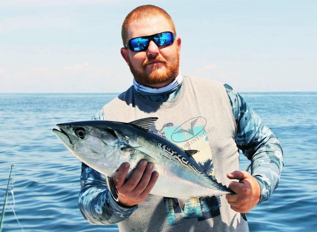 Tuna fishing: A smiling angler holding a Little Tunny