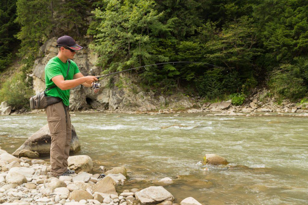 man fishing on a rocky river