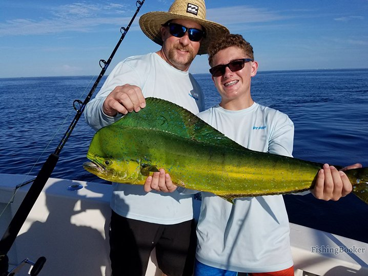 A teenage boy and his dad holding a Mahi Mahi which they caught on their fishing trip out of Marathon Key.