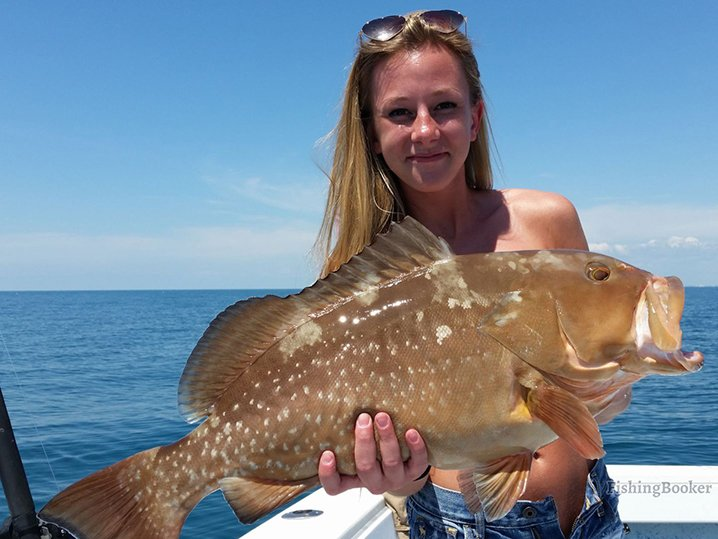 A smiling lady angler holding Grouper which she caught on her fishing trip out of Marco Island.
