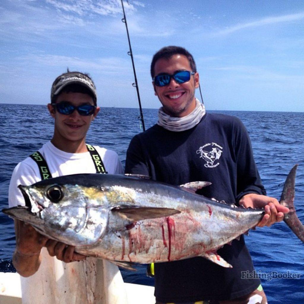 Two anglers holding a Blackfin Tuna
