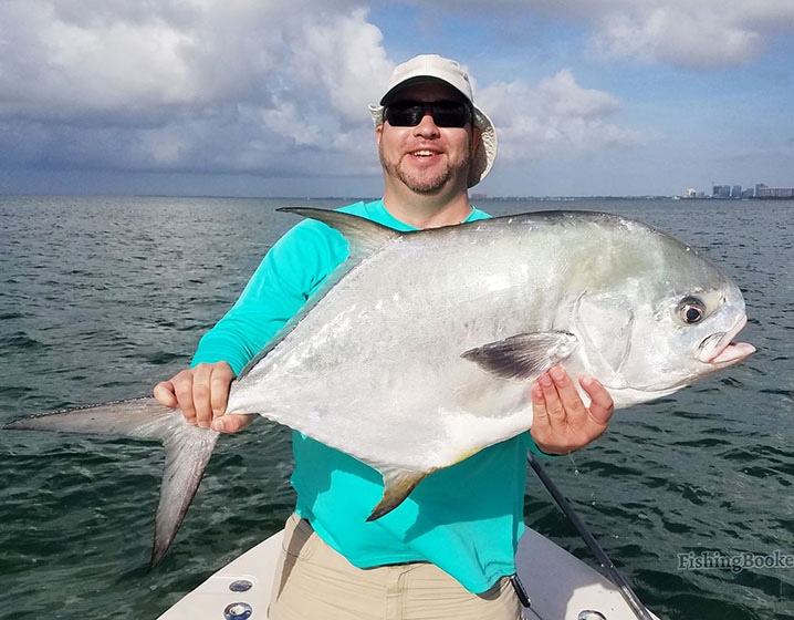 A smiling angler holding a Permit with Miami cityscape in the background
