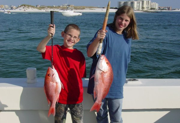 Destin fishing: A girl and boy angler holding Red Snapper