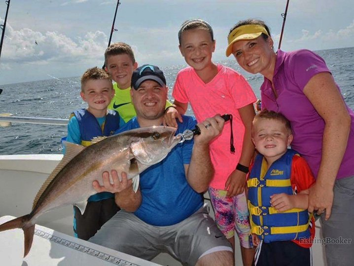 Parents and four kids on a family fishing charter in Myrtle Beach, holding an Amberjack.