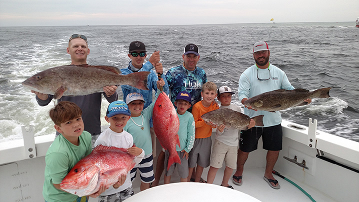 A group of anglers at the back of a fishing charter