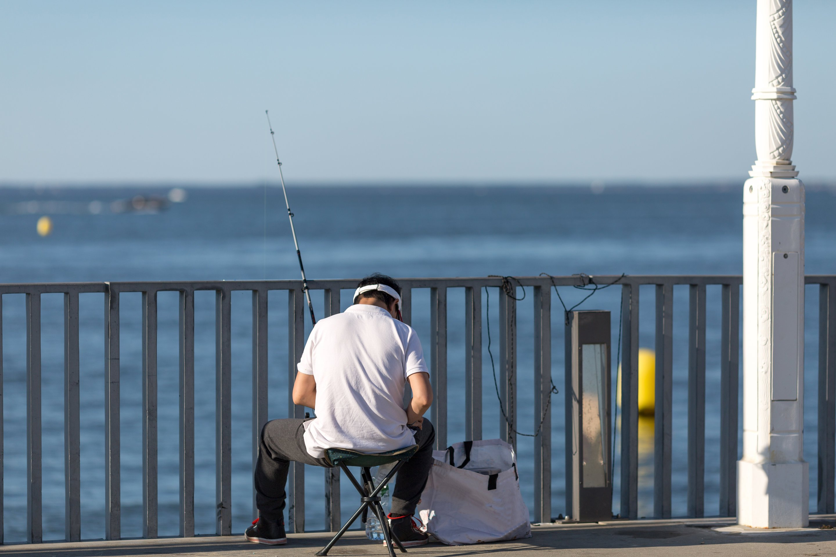 a pier angler adjusting his fishing gear