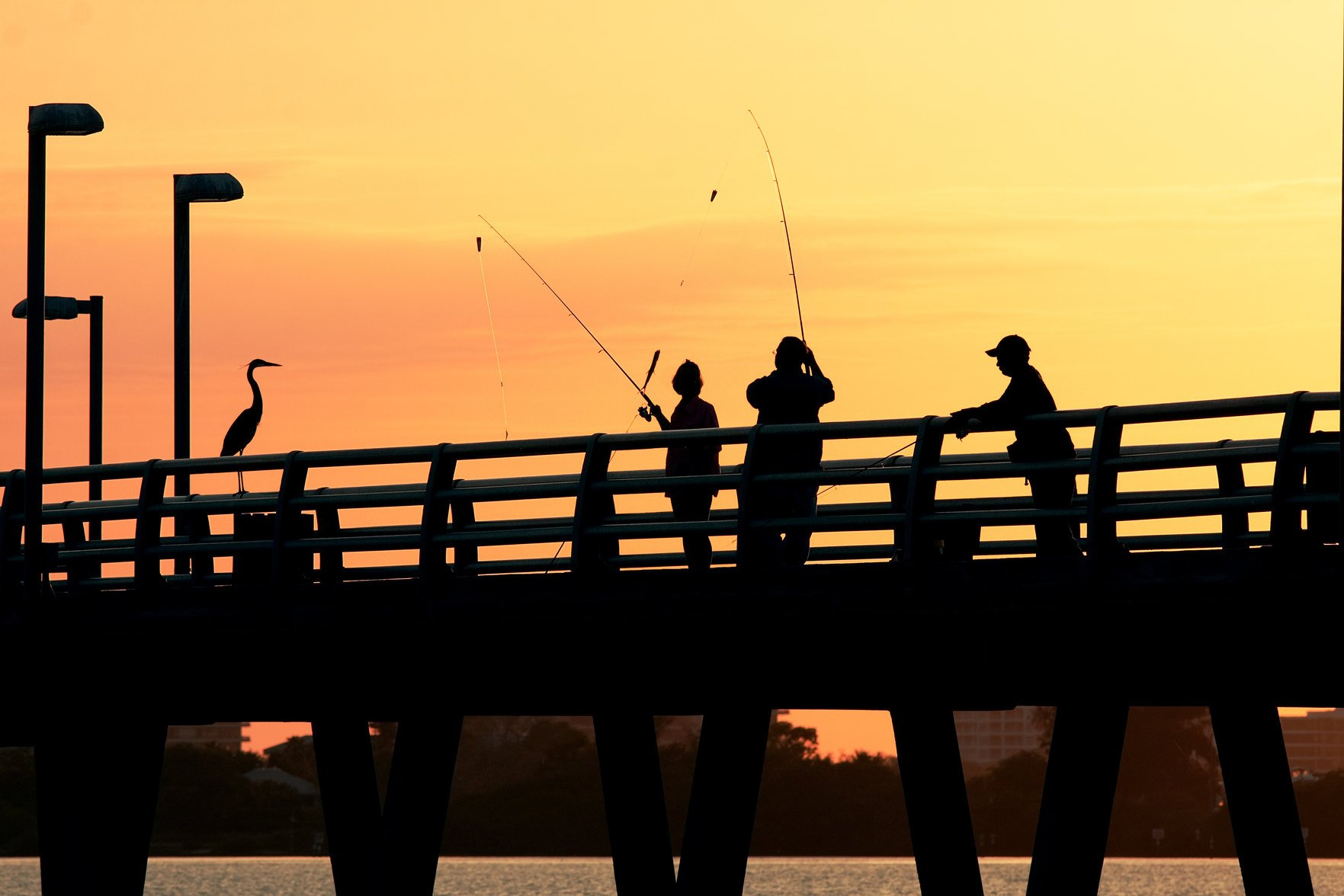 three anglers pier fishing at sunset