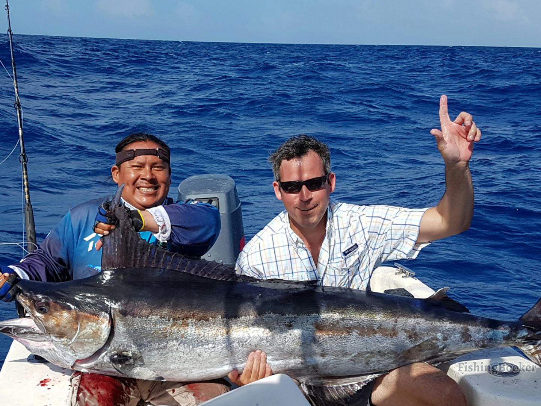 Playa del Carmen big game fishing> An angler holding a Marlin he caught on his fishing trip.