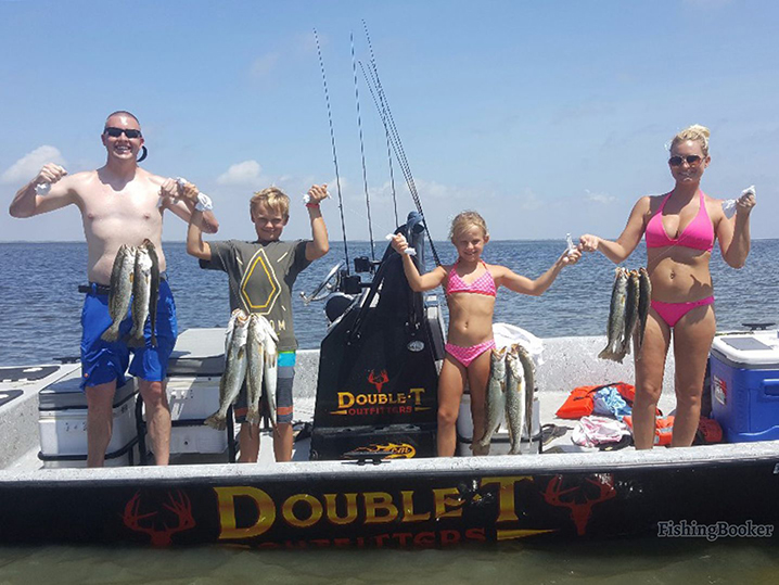 A family on their fishing trip in Port Aransas holding Speckled Trout.