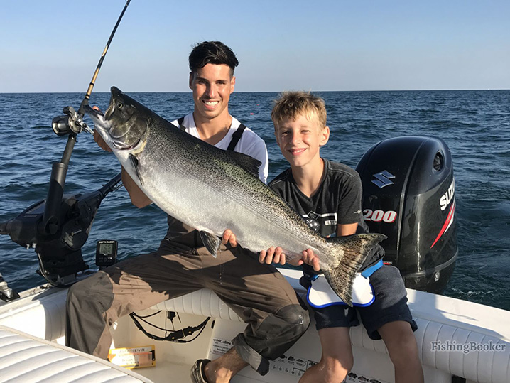 A dad and his son holding a Salmon they caught on their family fishing trip in Port Washington.