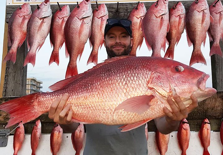 Angler holding a Red Snapper with a rack behind him filled of other Snappers, all caught aboard a party boat in Destin, Fl.