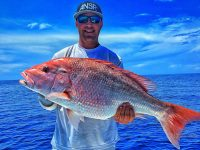 A smiling fisherman holding a big Red Snapper caught in the Gulf of Mexico.