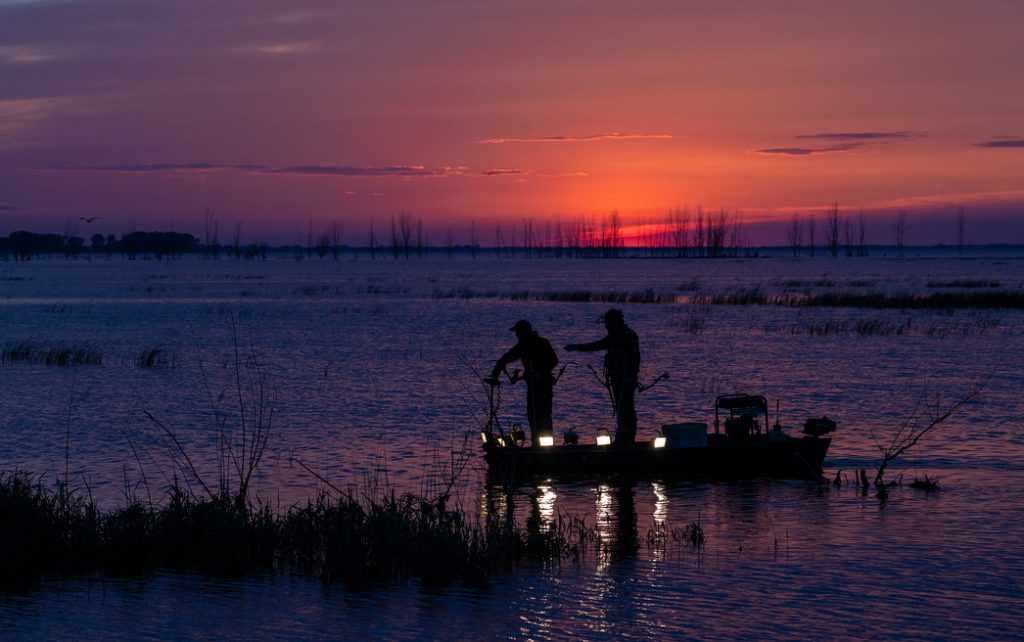two bowfishers on a small boat, fishing with the sunset in the background