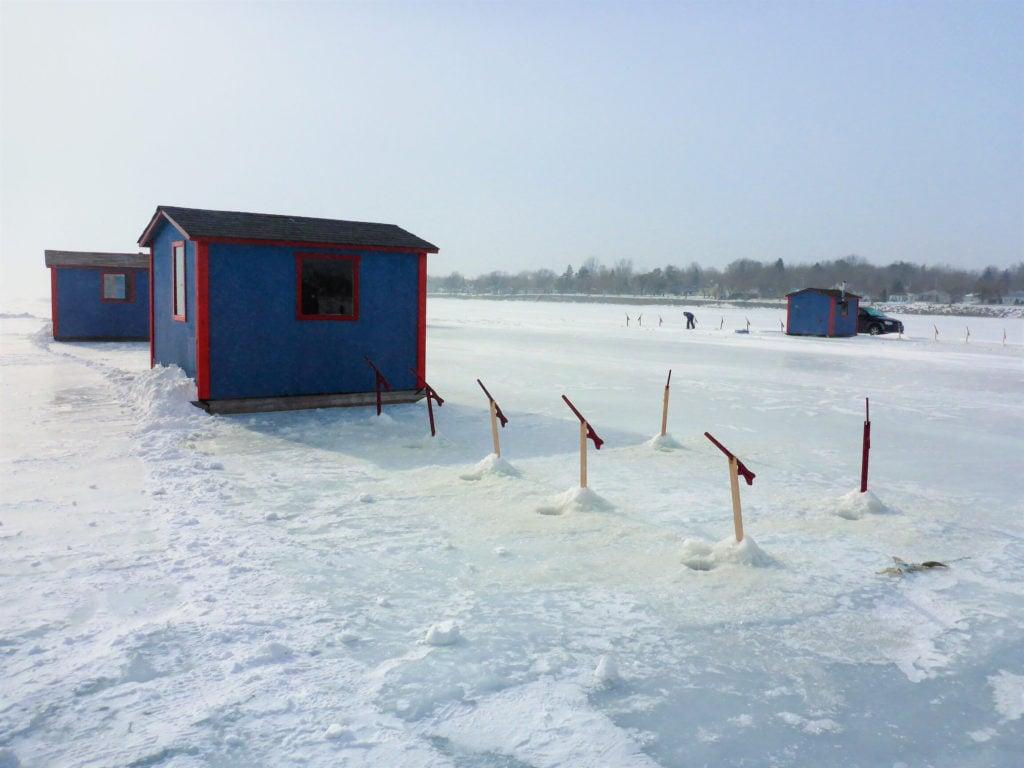 ice fishing tip ups spread near a shanty on frozen Lake Champlain