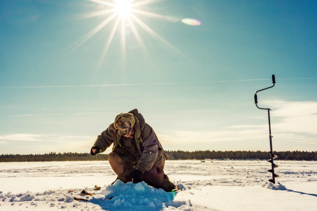 An angler dropping his line into a hole in the ice. Ice drill next to him in ice