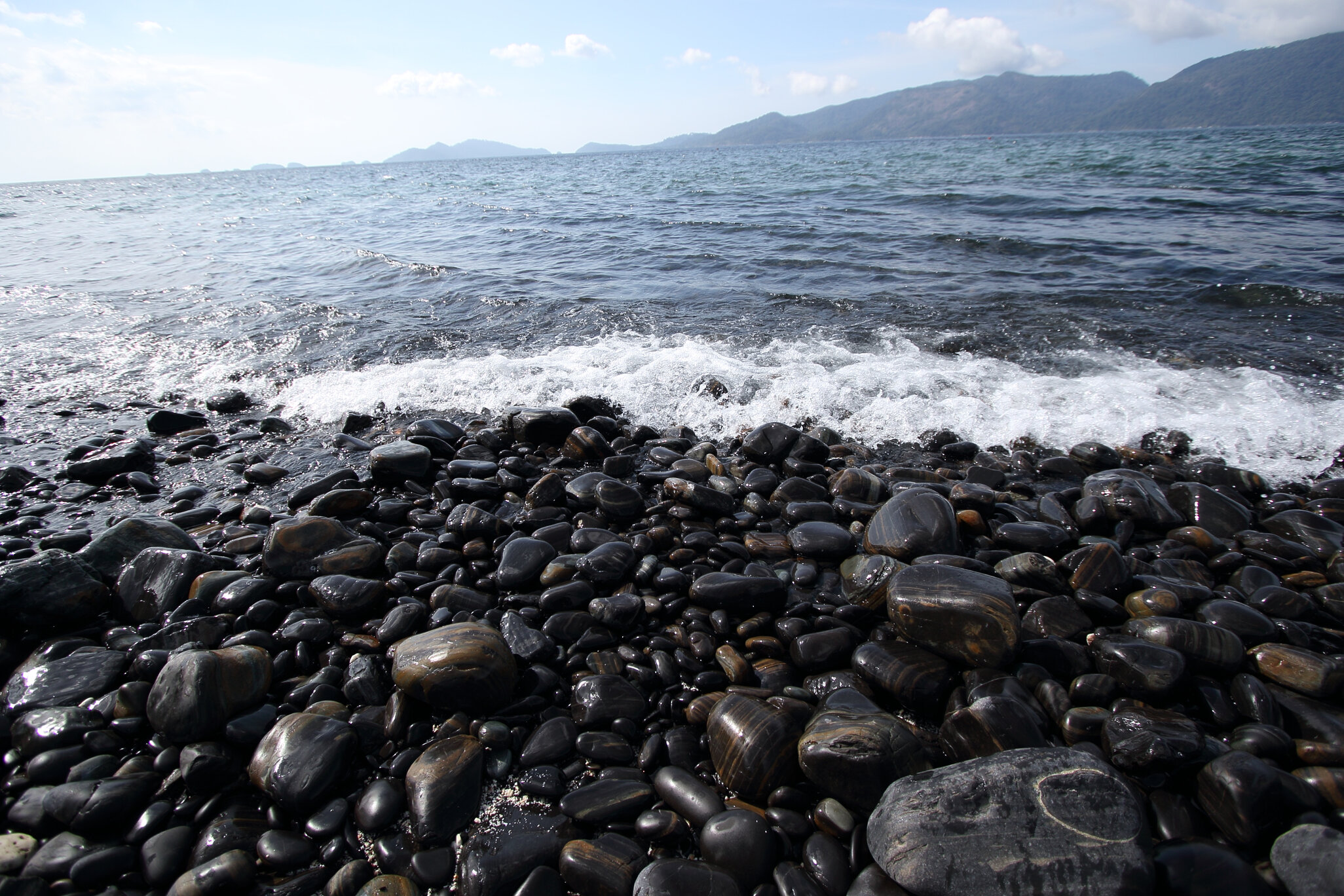 Waves crashing against black pebbles on a beach in Koh Hingham which is a haunted fishing destination