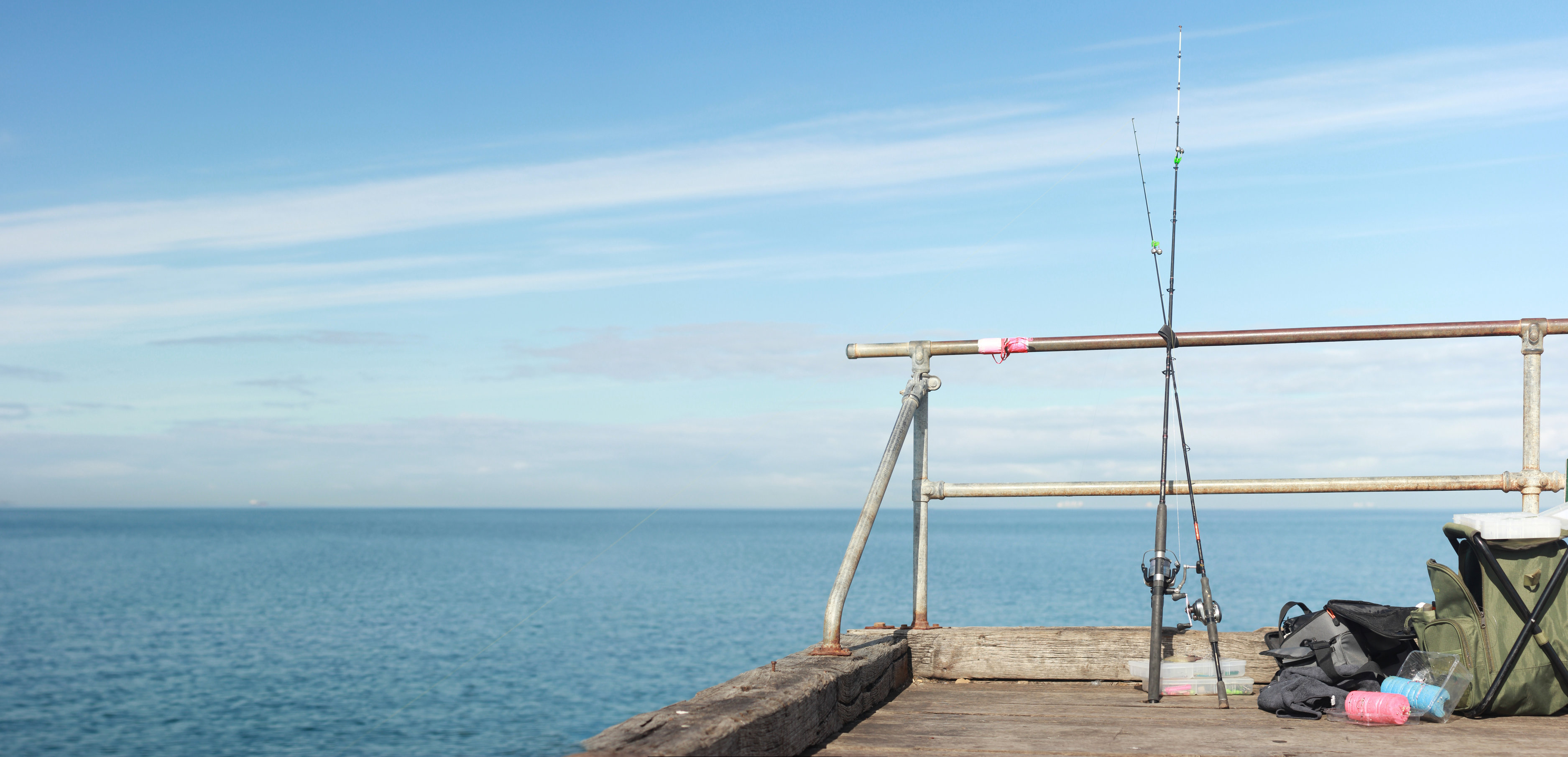 two fishing rods on a fence with the blue sea in the background