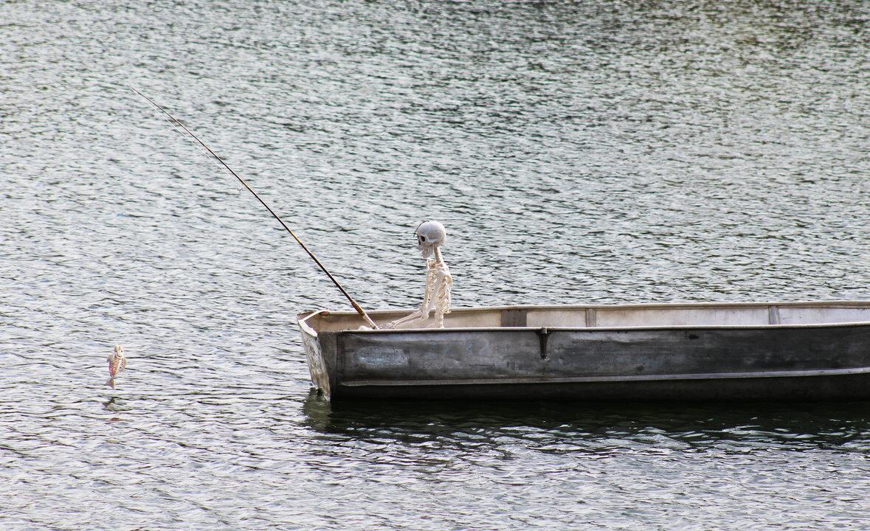 A Halloween human skeleton fishing for a fish skeleton
