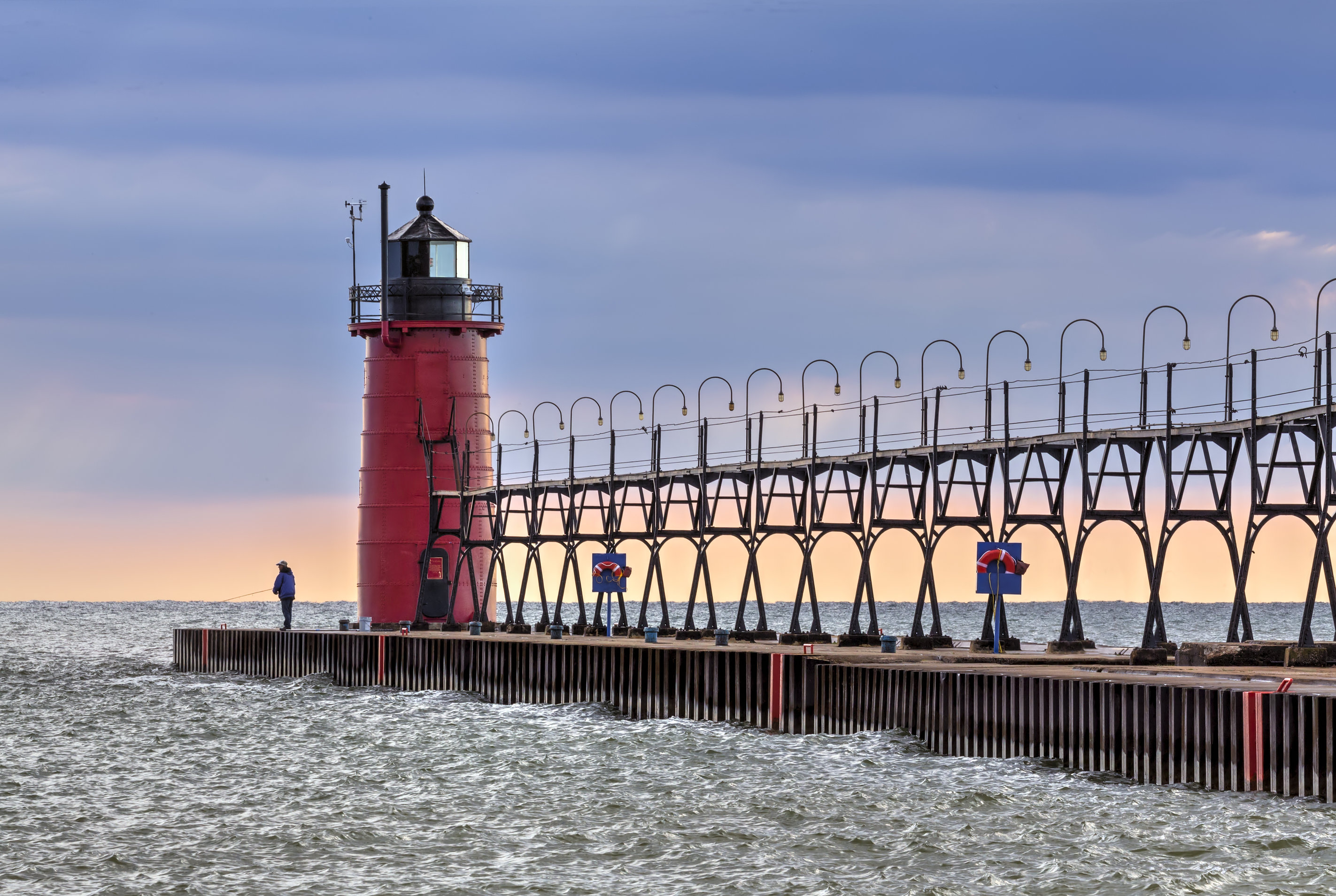 An angler fishing on Lake Michigan, one of the best fishing spots near Chicago, in South Haven right next to the Lighthouse after the storm