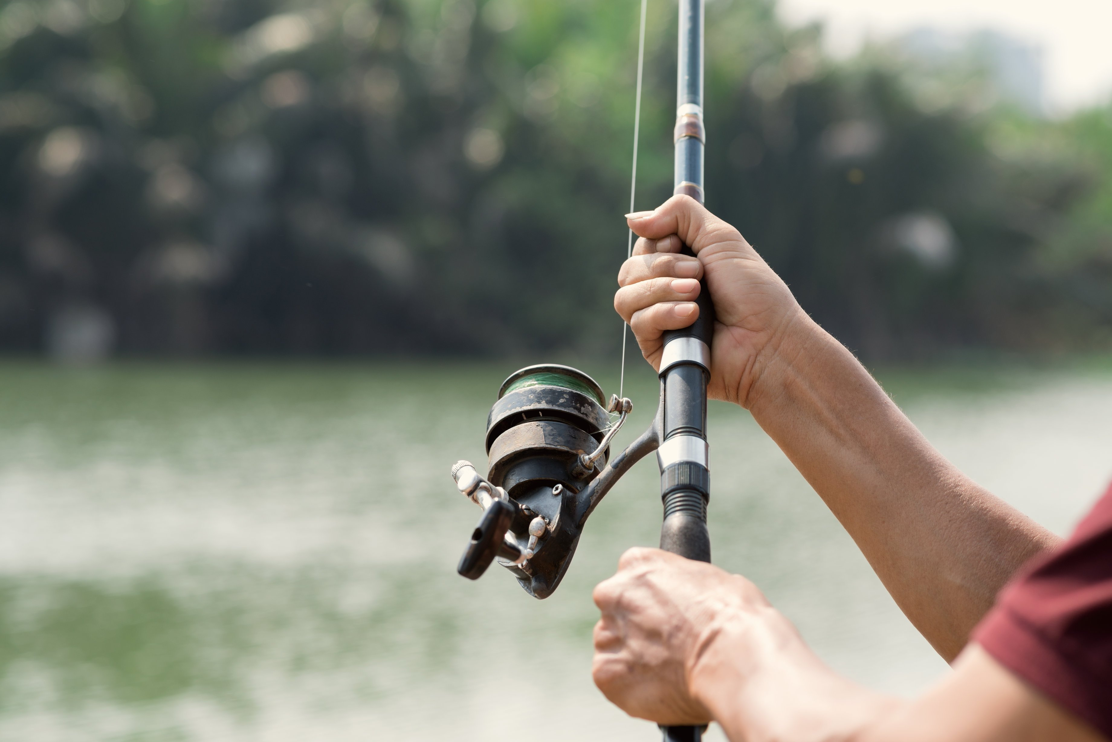 a closeup of a fishing rod being held by an angler