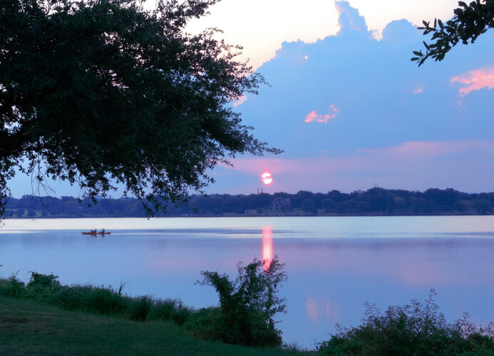 A sunset on a White Rock Lake, a haunted fishing destination in Texas