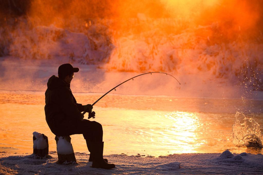 An angler fishing on an unfrozen lake in winter
