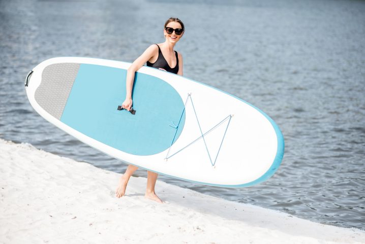 A woman carrying a stand up paddle board on a beach by the water