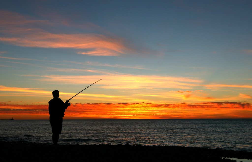 A man shore fishing on a beach at sunset