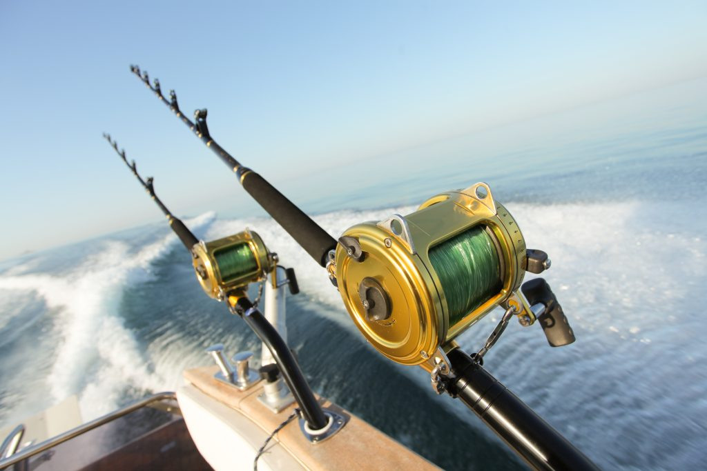 Fishing rods and reels on the side of a boat cruising on the sea