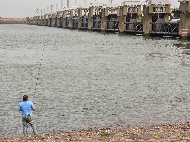 Man fishing next to the Great Dike of Oosterschelde