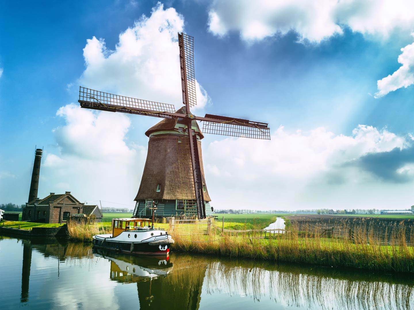 A boat on the waters of the Netherlands overlooking a big windmill