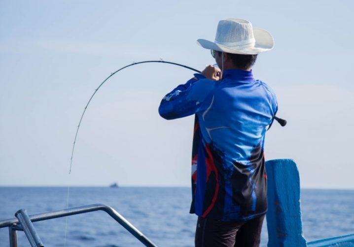 An angler in a blue shirt and a white hat holding a bending slow pitch jigging rod over the side of a boat