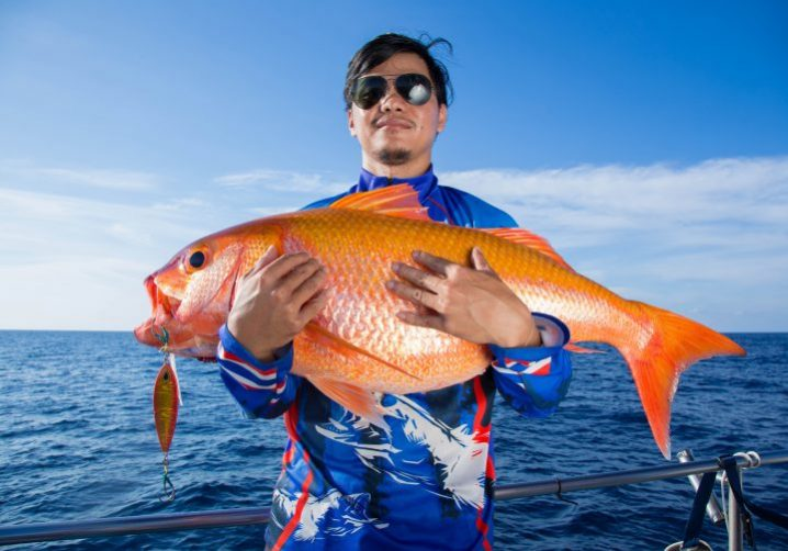 A man in a blue shirt and sunglasses holding a large orange fish with a slow pitch jig hanging out of its mouth