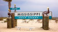 A Mississippi Gulf Coast sign on a beach with birds on it