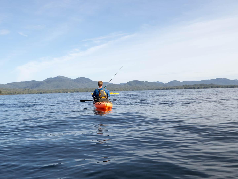 A man kayak fishing on a bay