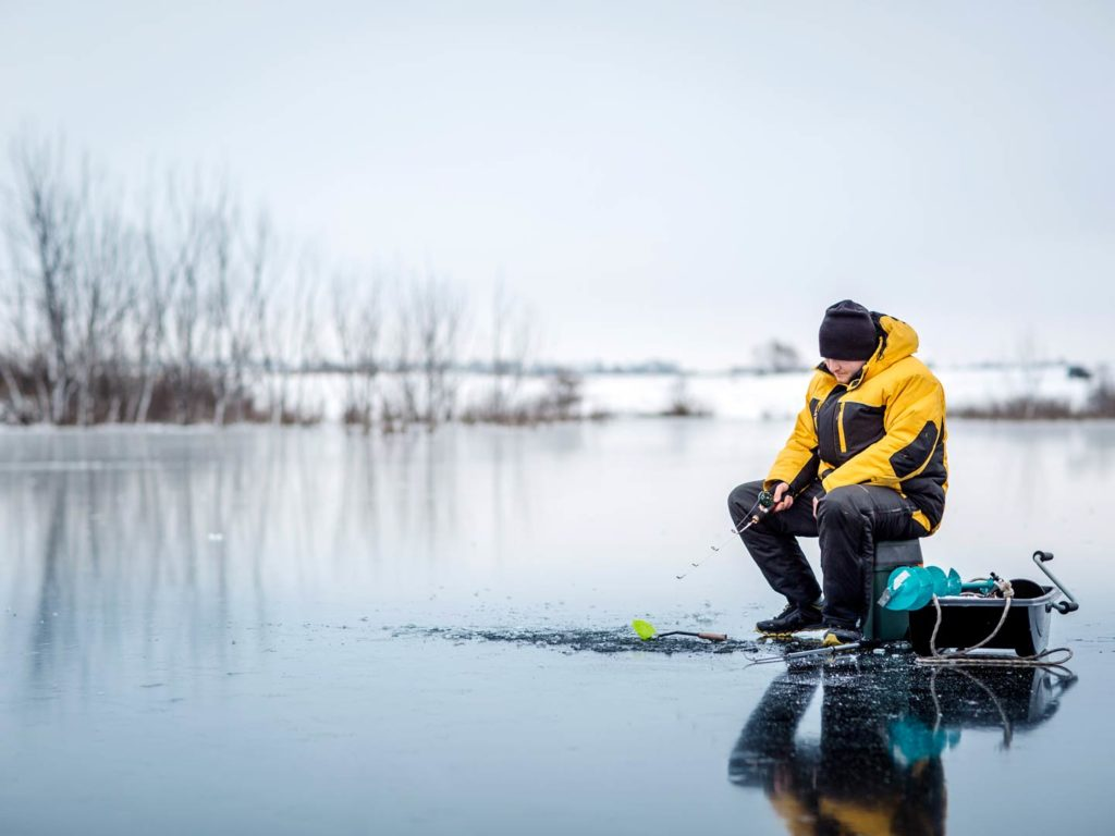 A man ice fishing in the Great Lakes