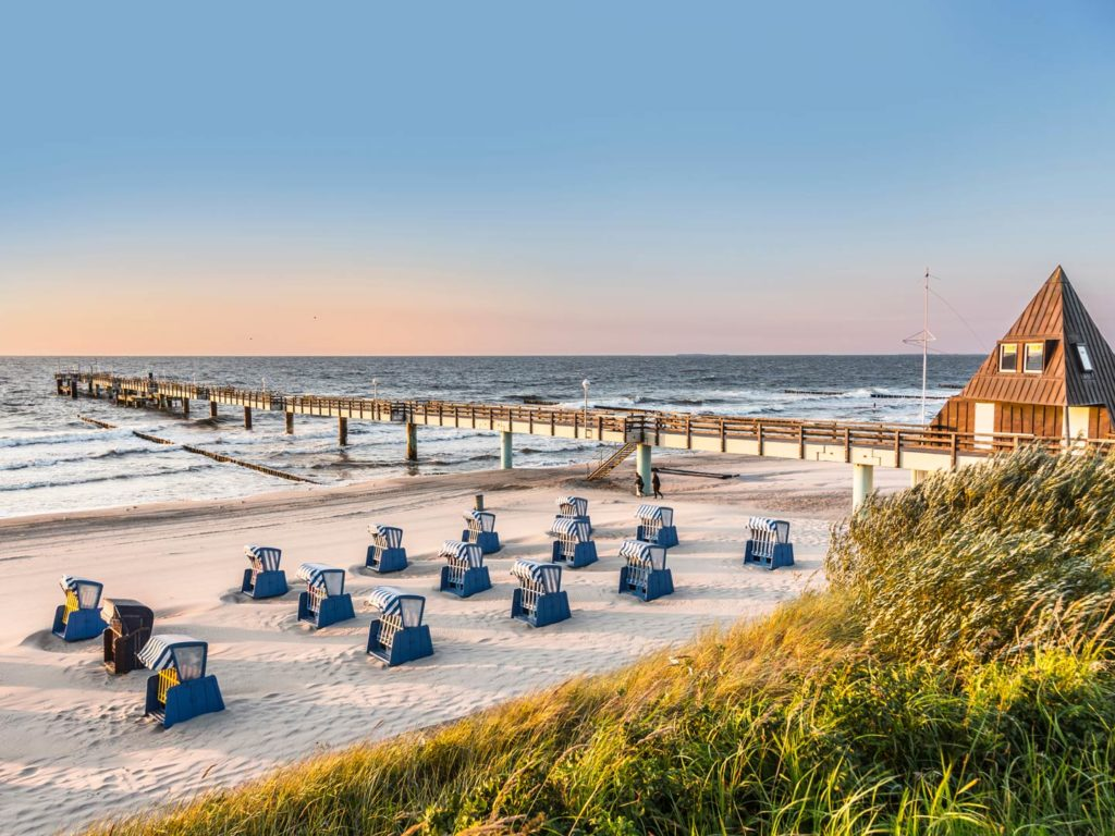 A Baltic Sea beach overlooking a fishing pier in the morning sun
