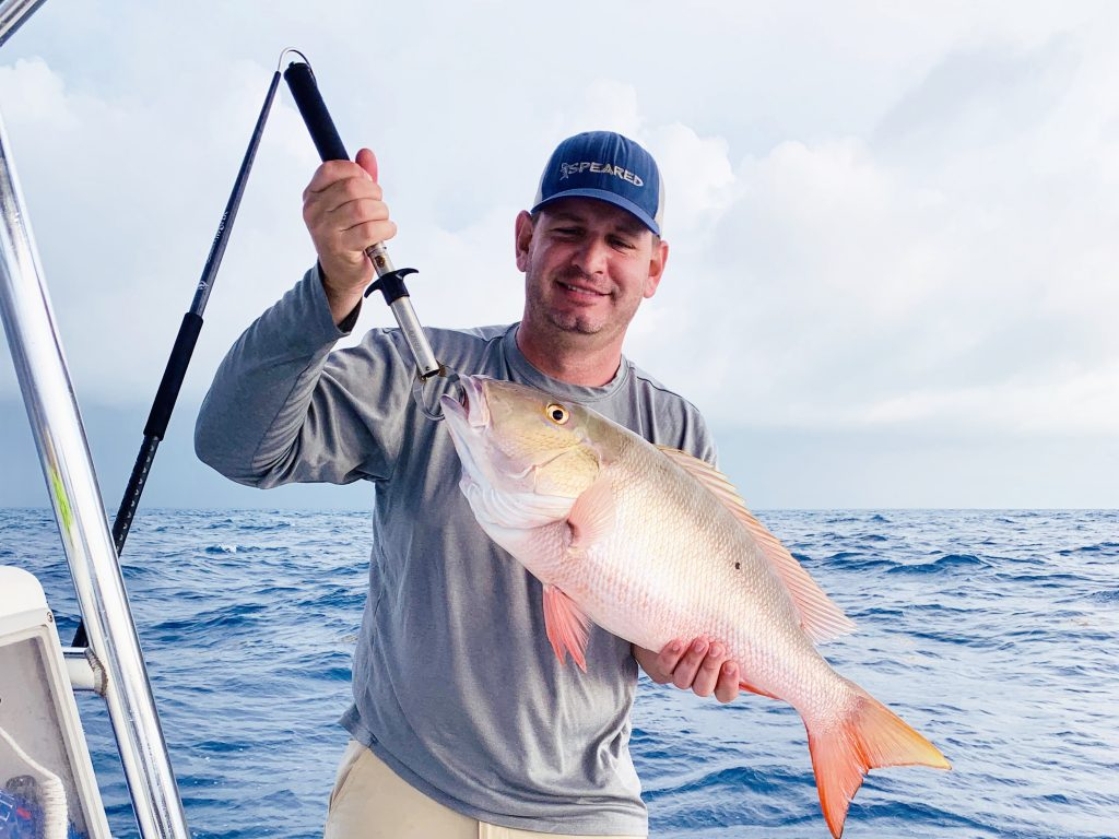 a smiling angler holding a snapper on a fishing boat